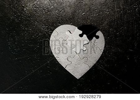 black and white heart shaped puzzle with missing piece on grunge background