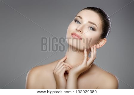 beautiful woman's face with blue eyes and clean fresh skin. girl touches her face with her hands