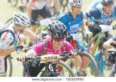 STOCKHOLM SWEDEN - JUNE 11 2017: Woman leading her mountain bike uphill at Lida Loop Mountain bike Race audience in background. June 11 2017 in Stockholm Sweden