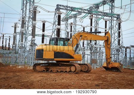 Excavator in industrial construction of electrical substation. Construction machinery works on industrial construction site