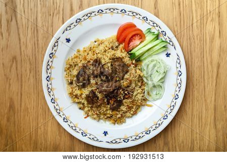 Uzbek pilaf with beef on a wooden background