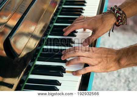 The Hands Of A Young Man Playing Piano On A Street Of City, Closeup.