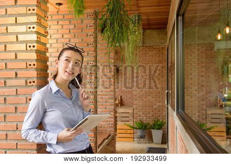 Business woman holding tablet PC with touchpad. young mixed race Asian Caucasian woman professional freelance lifestyle work out of office.
