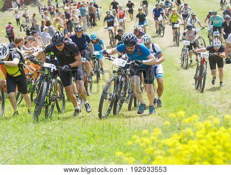 STOCKHOLM SWEDEN - JUNE 11 2017: Group of men leading his mountain bike uphill competitors behind at Lida Loop Mountain bike Race audience in background. June 11 2017 in Stockholm Sweden