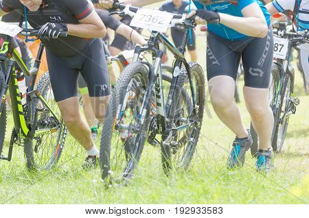 STOCKHOLM SWEDEN - JUNE 11 2017: Man leading his mountain bike uphill competitors behind at Lida Loop Mountain bike Race audience in background. June 11 2017 in Stockholm Sweden