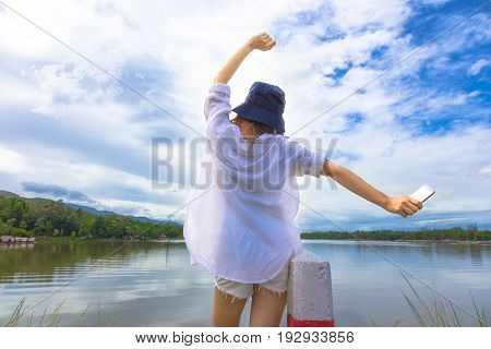 back of young happy woman in white shirt and short holding up her hands joyfully with her phone in her hand in front of a beautiful lake with view of white clouds and blue sky concept of freedom travel wireless connection or modern lifestyle for young gen