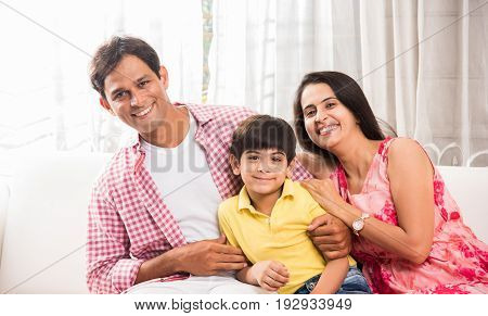 Candid Portrait of smart indian family of four while sitting on sofa. Indian or asian family group photo. Selective focus