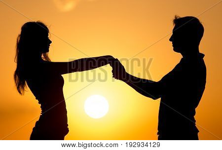 Silhouette of a guy and a girl at sunset .