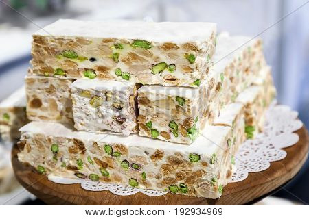 Pieces of white nougat cut and blocked served on a wooden tray.