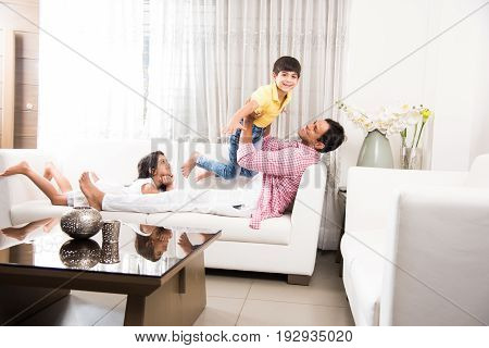 Happy Indian father playing with son while lying on sofa in living room at home. Asian Young man playing with small boy. Flying child enjoying playing with dad while sister watching