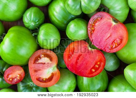 Red Tomatoes Cut In Half On Immature Green Tomatoes Top View. Bright Red-Green Color.