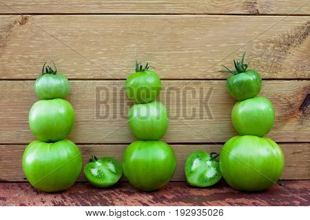 Immature Green Tomatoes On Wooden Brown Board Top View And Close Up.