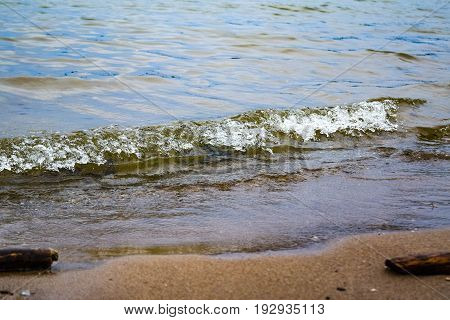 Wave runs on the sandy shore close-up background