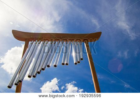 Wind Musical Chimes On The Background Of Blue Cloudy Summer Sky.