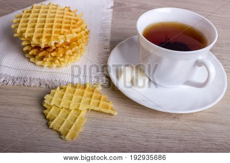 Breakfast With Waffles Stack On Napkin And Pieces Of Waffle With White Cup Of Black Tea On Wooden Su