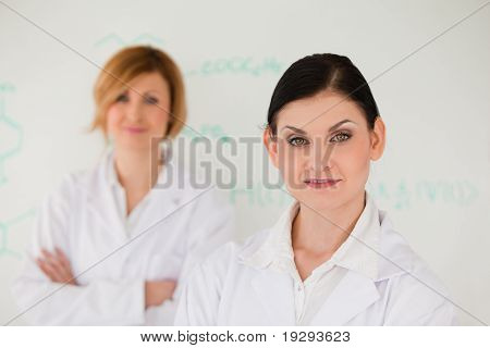 Two scientist women posing in front of a whiteboard