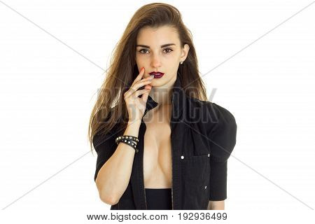 Portrait of an attractive brunette who poses in the Studio with unfastened black jacket and dark lipstick on your lips is isolated on a white background.