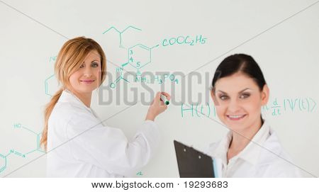 Scientist posing while another writes a formula on a whiteboard