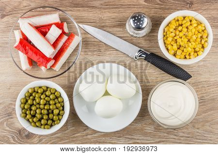 Crab sticks in saucer peeled eggs sweet corn mayonnaise salt and knife on wooden table. Top view
