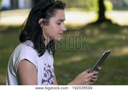 She Relaxes In Nature While Looking Over The Digital Tablet, What Her Friends Do