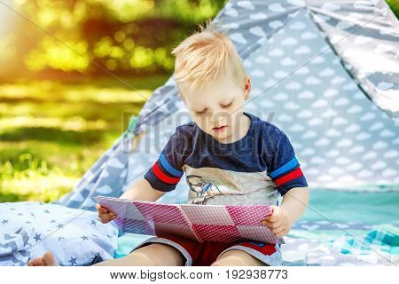 A little kid reads a book in the park. Boy preschool. The concept of childhood learning and lifestyle.