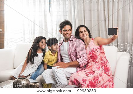 Family time - Indian family taking selfie picture, wife clicking selfie with smartphone of a happy young family of four, husband, wife and two kids, while sitting indoor on sofa