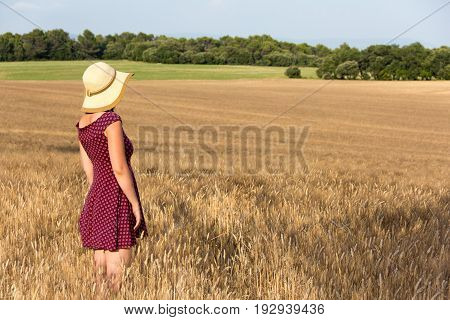 Beautiful girl in sundress and straw hat standing in ripening wheat filed starring in distance