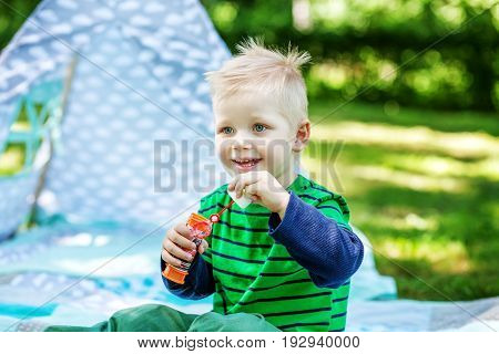 Little boy blowing bubbles in the park. The concept of lifestyle and childhood.