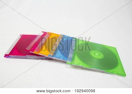 Background of some CD or DVD colorful compact discs. discs in colorful boxes isolated on white background.