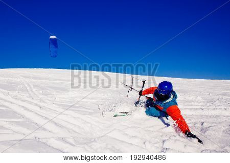 Skier with a kite on fresh snow in the winter in the tundra of Russia against a clear blue sky. Teriberka, Kola Peninsula, Russia. Concept of winter sports snowkite on ski.