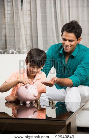 Indian Father and Son putting coins into pink piggy bank, teaching financial planning