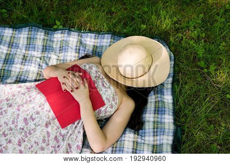 Woman sleeping in the grass outside while reading a book