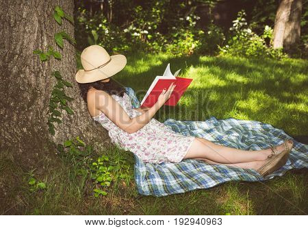 Woman relaxing on a tree reading a book outside in the grass