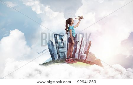 Cute kid girl on city floating island playing with retro plane model