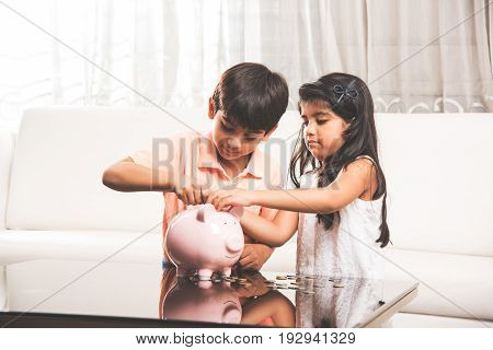 indian small kids with piggy bank, asian little brother and sister putting coins inside piggy bank planning finances