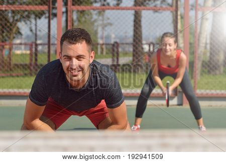 Couple playing doubles at the tennis court. Healthy fitness concept with active lifestyle.