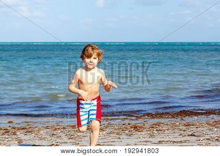 Blond little kid boy having fun on Miami beach, Key Biscayne. Happy cute child playing with sand and running near ocean.