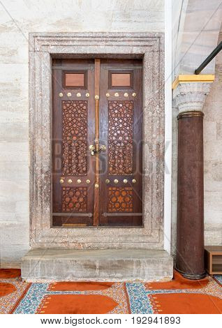 Wooden aged engraved door and marble wall Suleymaniye Mosque Istanbul Turkey
