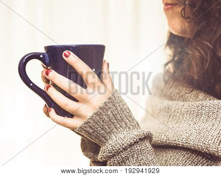 Woman holding a hot cup of coffee or tea in the morning sunlight.  Morning start concept.