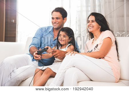 Family time - Happy Indian family- father, mother and daughter playing a video game at home. Asian family playing video game with joy stick or controller