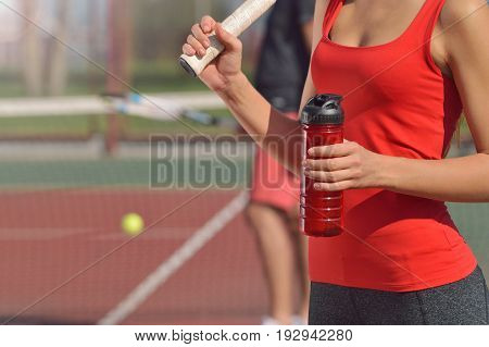 Young adult woman with racket and red bottle of water on the tennis court. Training man on the background. Healthy fitness concept with active lifestyle.