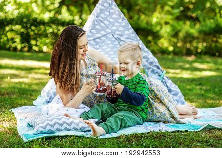 Happy mother and little son drink juice. The concept of lifestyle and childhood.