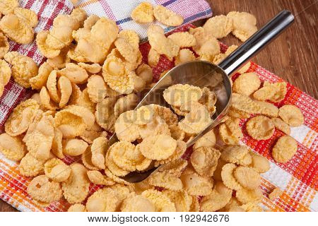 Pile of cornflakes and scoop close up
