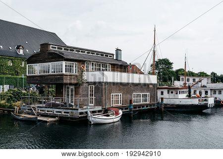 Copenhagen Denmark - August 12 2016: Picturesque house boat in the port of Copenhagen a cloudy summer day