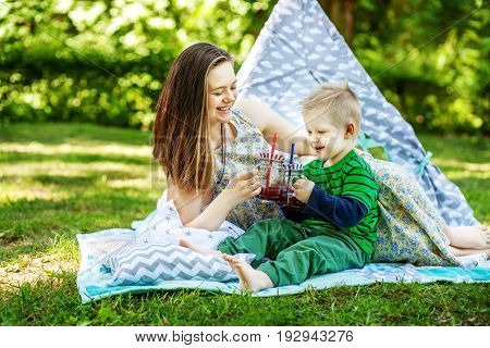 Happy mother and little son drink juice on a picnic. The concept of lifestyle and childhood.