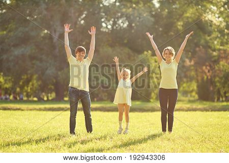 Happy family in park with hands up. Mother, father and daughter on green grass in nature.