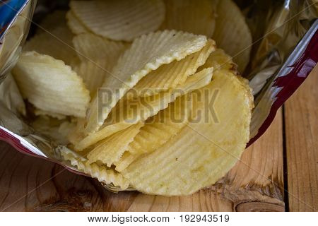 Yellow salted potato chips on wood table