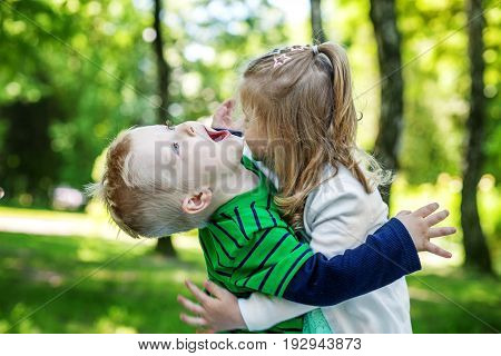 Brother and sister play in the park. Preschool children. 2-3 years. The concept is childhood and family.