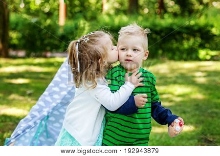 Little girl kisses friend. 2-3 years. Girl and boy. The concept is childhood and family.
