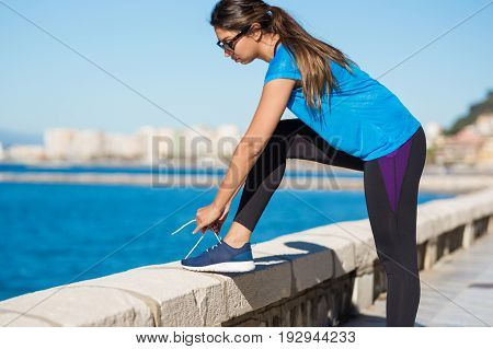 Young Sportswoman Tying Shoelace Outside
